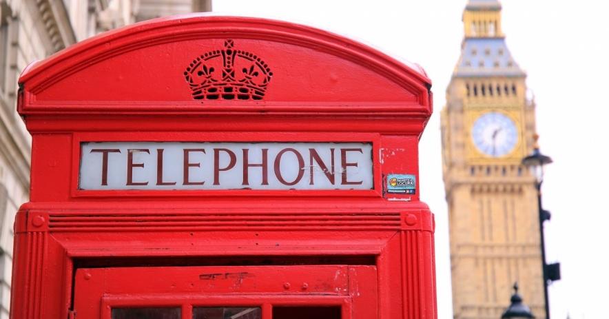 Cabina de teléfono roja con la famosa cama grande de Londres en el fondo