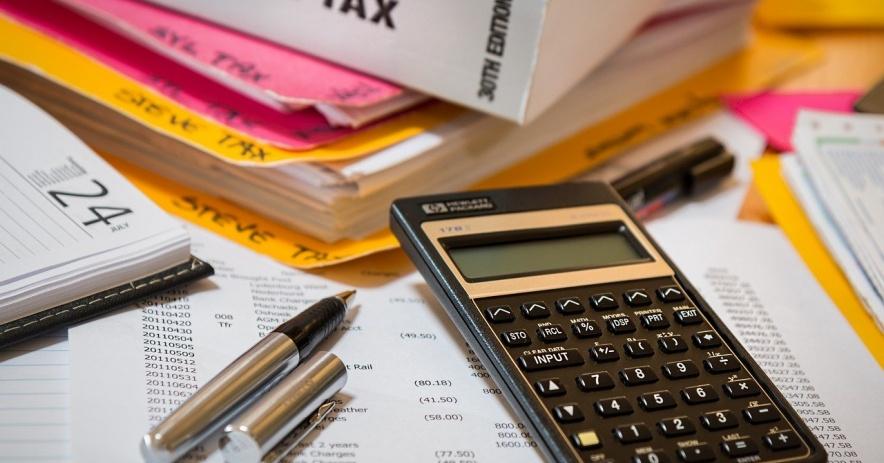 Libro con Impuesto sobre la Renta en el lomo, calculator, bolígrafo, calendario y carpetas sobre una mesa.