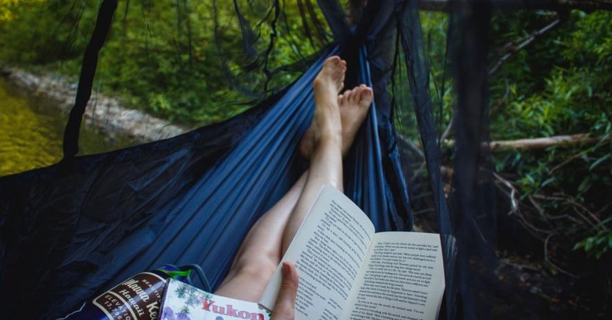 persona sentada en una hamaca leyendo un libro