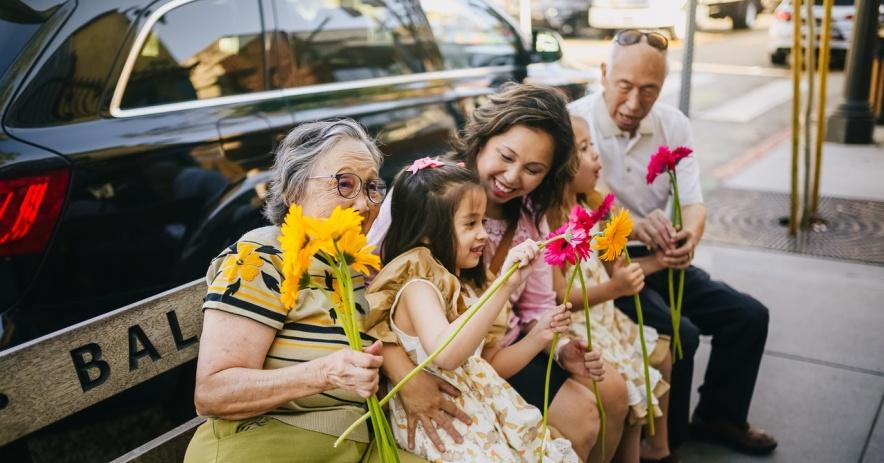 Una familia asiática sonriente de una madre, dos hijos y dos abuelos sentados en un banco de la ciudad con flores.