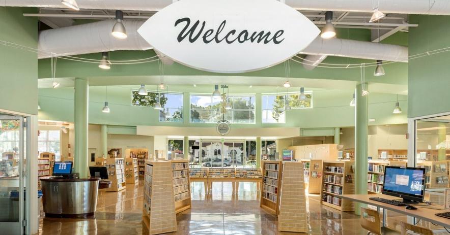 Biblioteca limpia y acogedora con un cartel de bienvenida permanente que cuelga del techo.