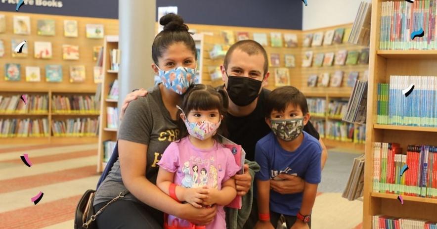 Una familia de cuatro posa para una foto dentro de la habitación de los niños en la biblioteca.