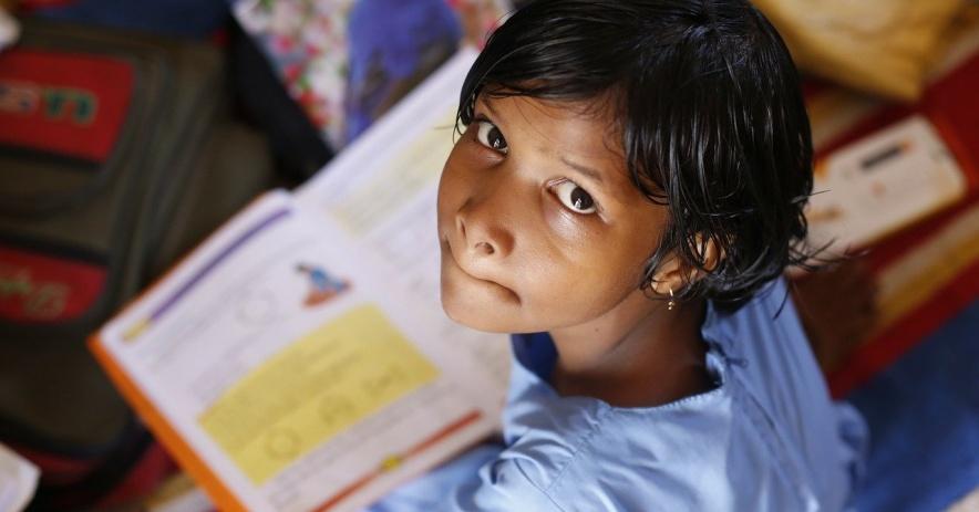 Niño con un libro abierto que está mirando a la persona de la cámara.
