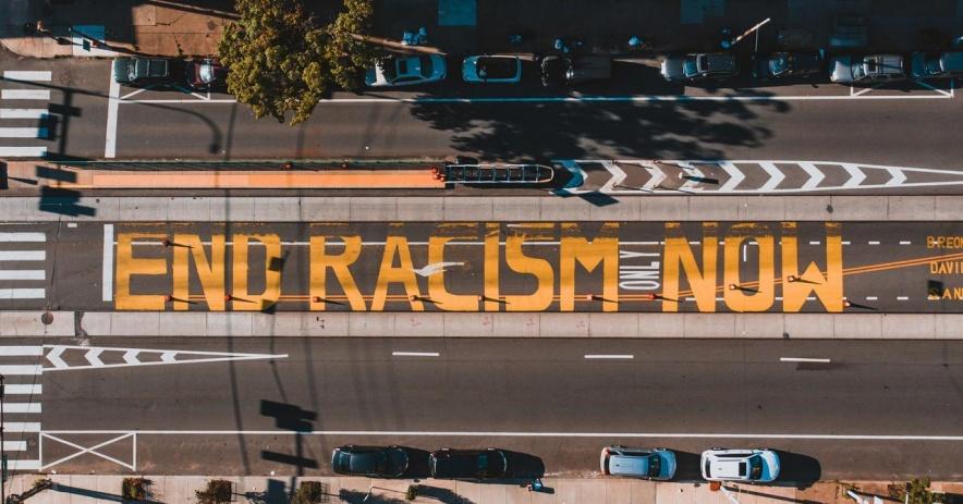 '結尾 Racism Now' 寫在街面上,從上面看。