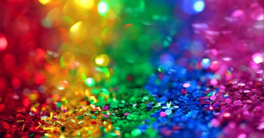 Montones de lentejuelas brillantes y atrevidas en rojo, amarillo, verde, azul y morado en rayas que se asemejan a la bandera LGBTQ Rainbow Pride.