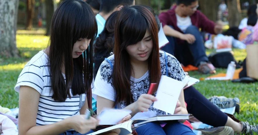 Dos chicas comunicándose sobre libros abiertos.