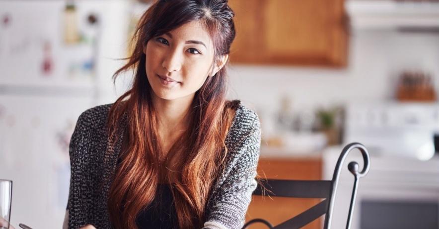 Adolescente asiática sentada a la mesa en la cocina mirando a la cámara