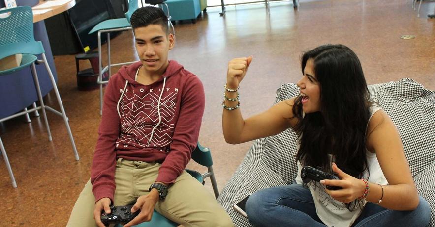 一個青少年玩家慶祝她的勝利tor當她的對手接受他在比賽中的失敗時 TeenHQ 玩家休息室。