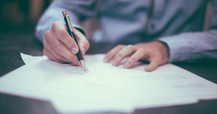 Estudiante en uniforme sosteniendo un bolígrafo y escribiendo un ensayo en papel de encuadernación.