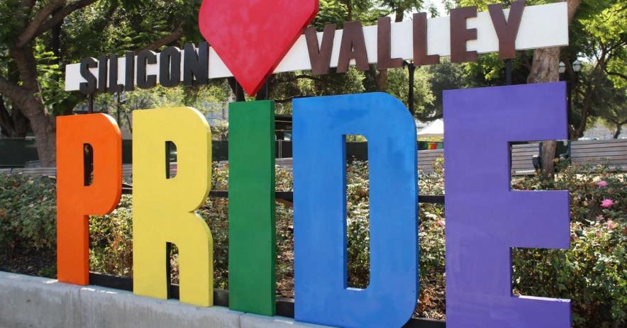 Una fotografía de un gran letrero que dice Orgullo de Silicon Valley. Las letras de la palabra orgullo están pintadas con los colores del arco iris con un corazón sobre la I.