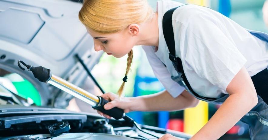 Adolescente rubia trabajando en un coche