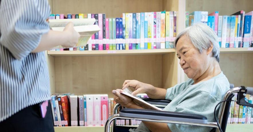 Người phụ nữ ngồi xe lăn kiểm tra sách mà nhân viên đã lấy cho cô ấy.