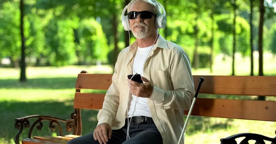Người đàn ông mù trên băng ghế công viên nghe eAudiobook từ điện thoại.