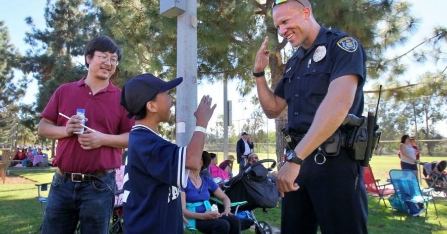 oficial de policía y niño se saludan