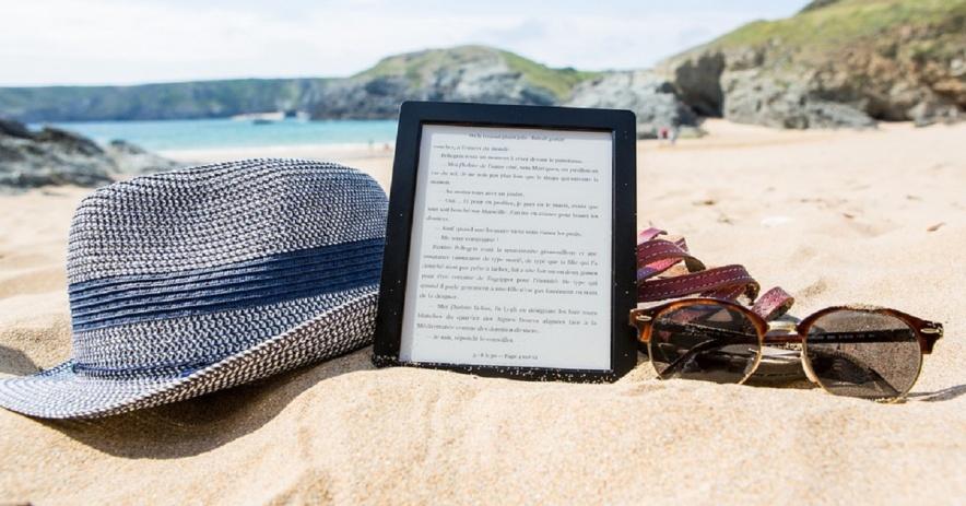 Thiết bị Kindle và một vài đồ cá nhân nằm trên bãi cát