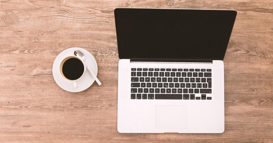 Hình ảnh của một máy tính xách tay và một tách cà phê ngồi trên bàn làm việc.
