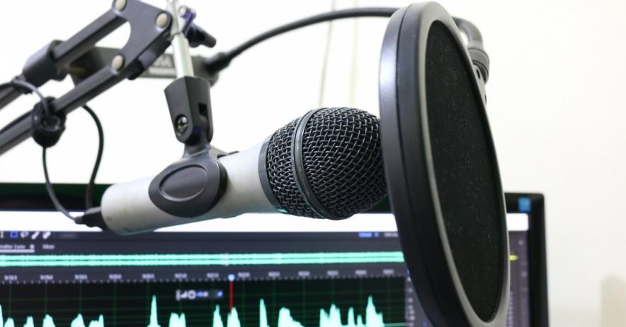 Micrófono de grabación con pantalla de computadora de fondo