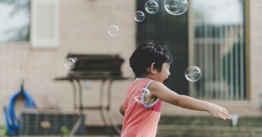 niño jugando con burbujas al aire libre