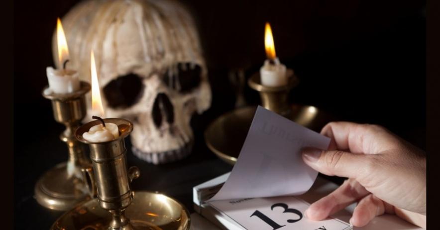 Calavera detrás de velas encendidas y un calendario que dice Viernes 13