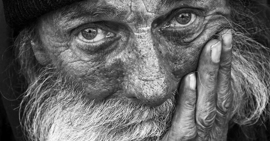 Imagen en blanco y negro de un hombre con un gorro de punto negro y barba blanca