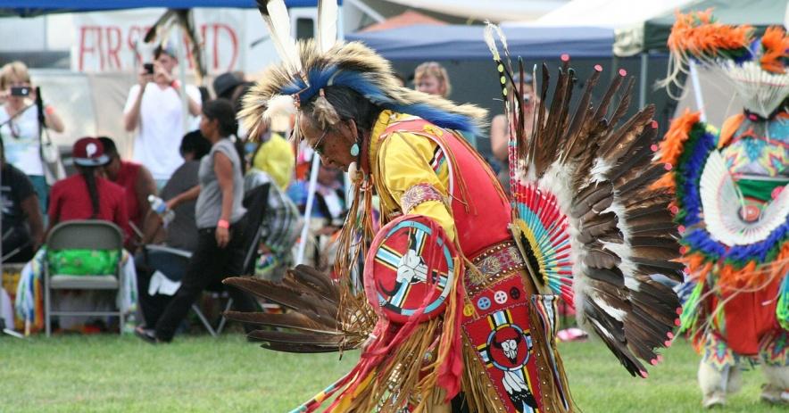 Hombre nativo americano en traje tradicional baila sobre un césped verde con gente y marquesinas en el fondo.
