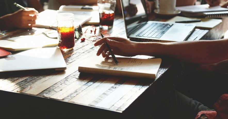 Mesa con papeles, libros, laptops, bebidas y personas reunidas (sin caras).