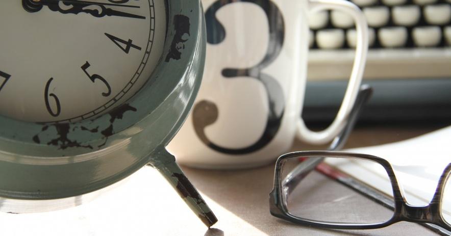 Un reloj analógico, una taza con un 3, un par de gafas, un libro y un teclado de fondo.