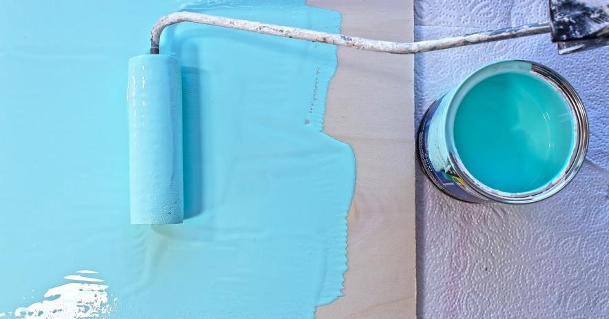 La pintura azul claro se aplica sobre una superficie de madera con un rodillo de pintura y una lata de pintura.