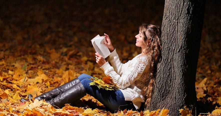 người phụ nữ đọc gần cây