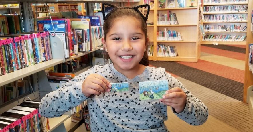 Niño sonriente sosteniendo su tarjeta SJPL dentro de una biblioteca.