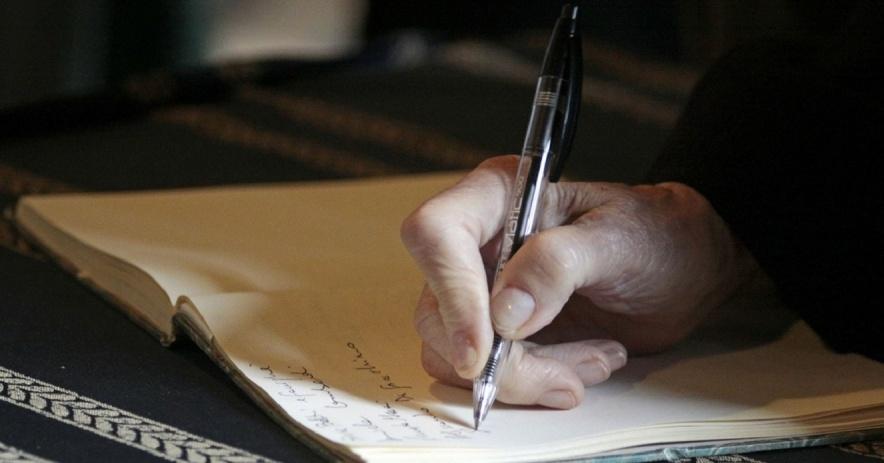 mano sosteniendo un bolígrafo escribiendo en un cuaderno