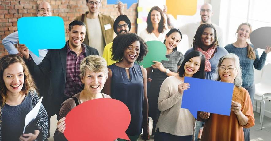 Diversos grupos de miembros de la comunidad sostienen diferentes colores de papel recortados en forma de burbujas de conversación.