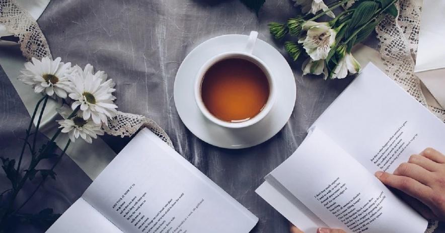 Hai cuốn sách đã mở, tách trà và tay người đọc.