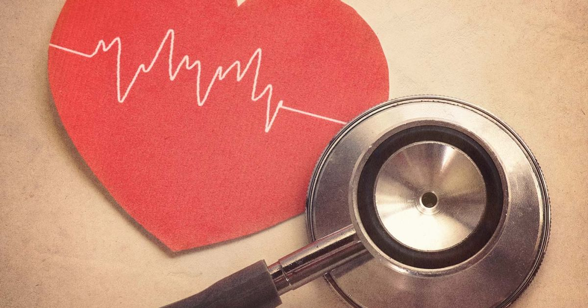 red paper heart and stethoscope atop a person's chest