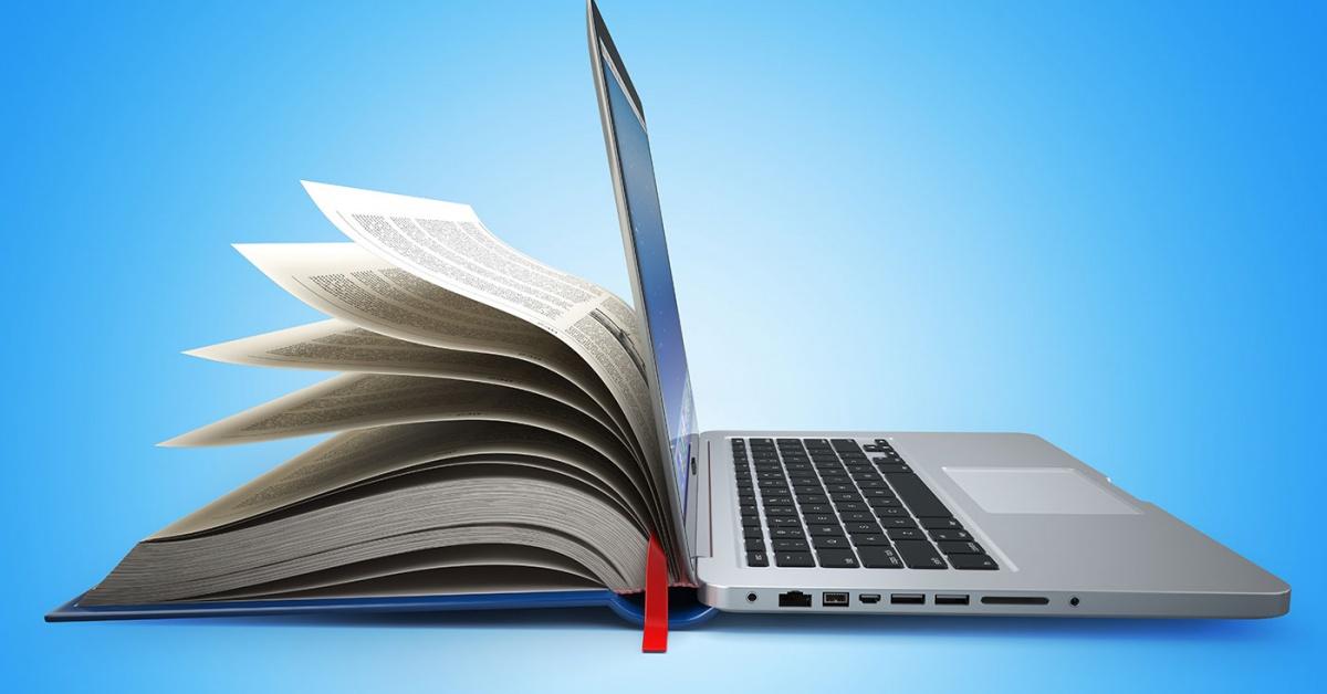 libro abierto tiene páginas en un lado y compuer en el otro.