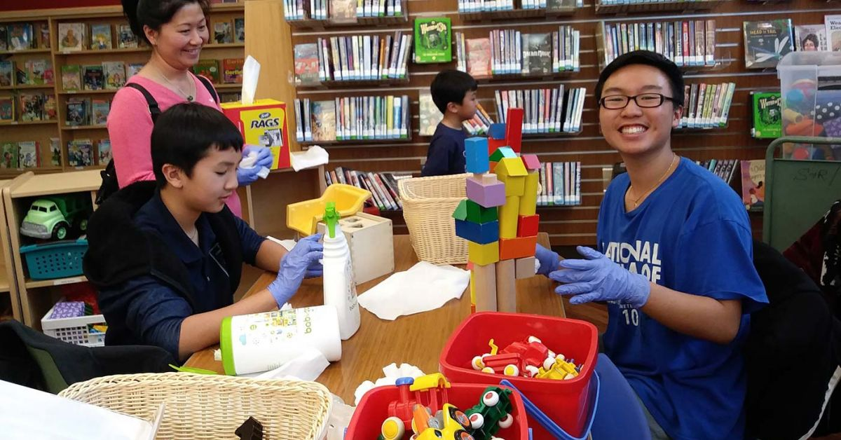 Family cleaning toys during volunteer event.