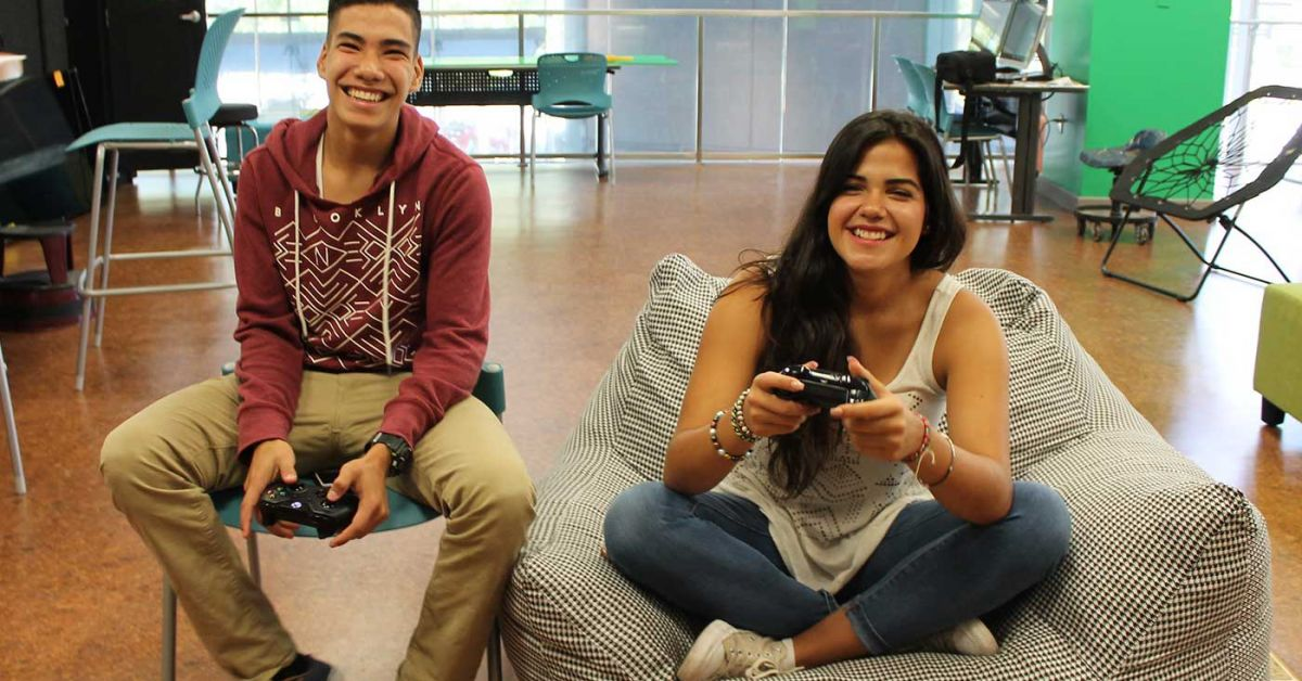 Teens chuckling while playing video games in comfortable TeenHQ seating.