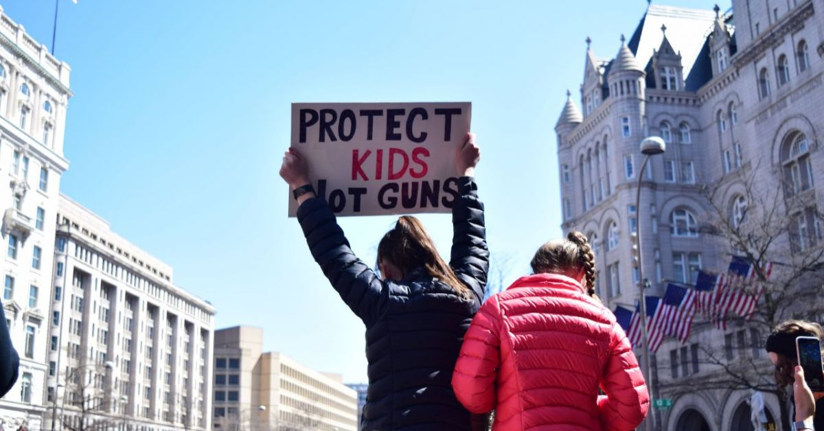 "Person holding a sign that reads ""Protect kids not guns"" at a rally march."