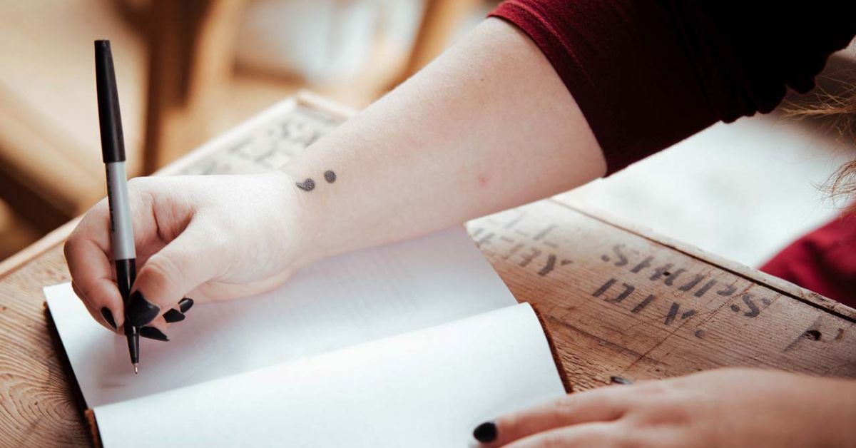 Mano escribiendo en un trozo de papel con un tatuaje de punto y coma en la muñeca.