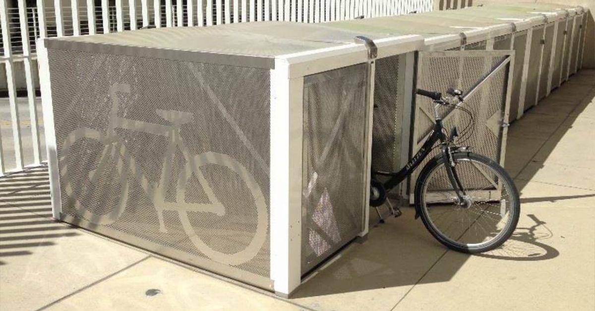 Fila de casilleros BikeLink plateados: uno con una puerta abierta y una bicicleta a medio camino.