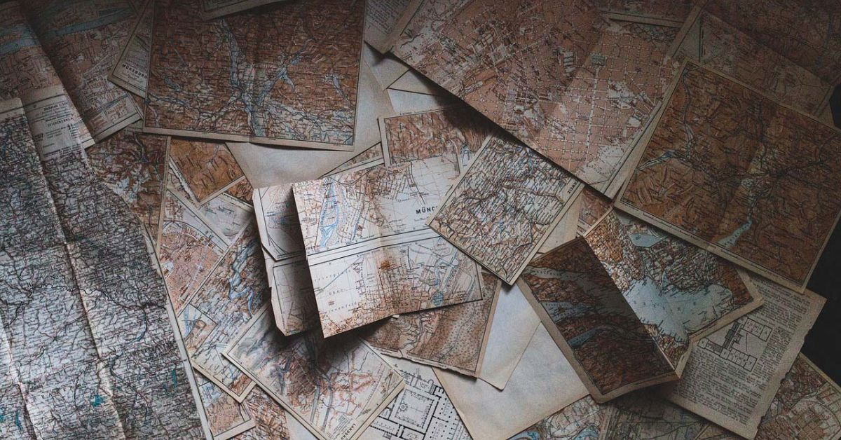 Yellowed maps scattered randomly.