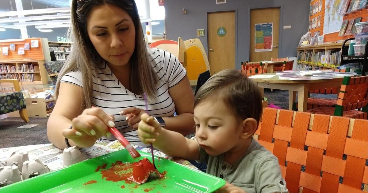 父母幫助她的孩子畫出非常餓的毛毛蟲的紅色部分。