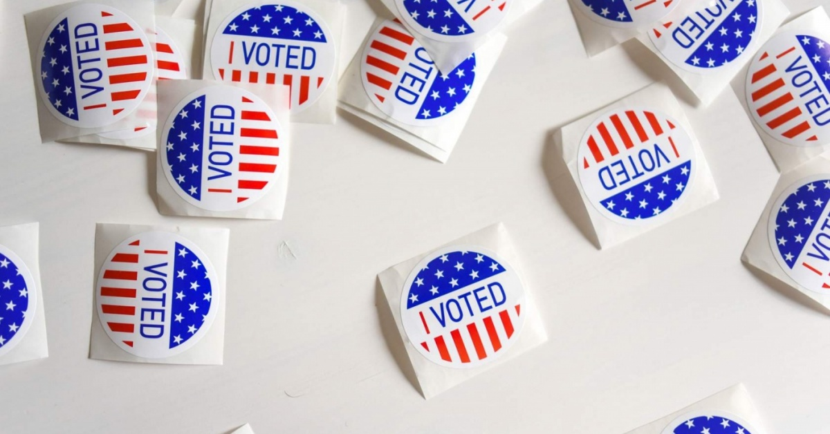 "Scattered ""I Voted"" stickers with the American flag on a white background."