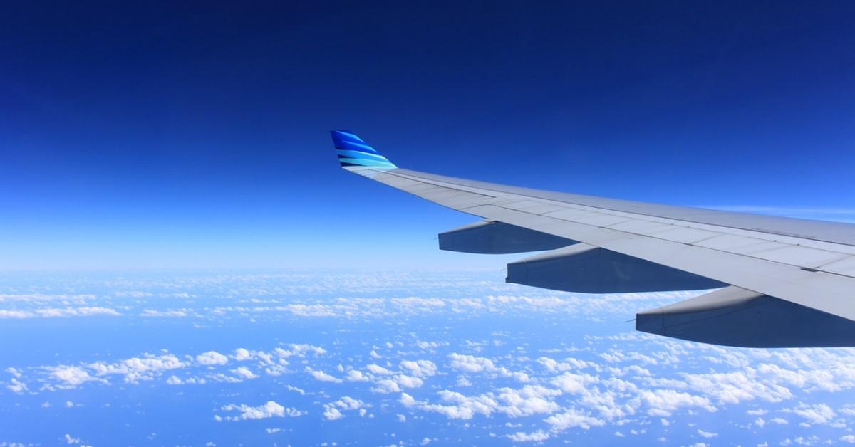 Quang cảnh một cánh máy bay với bầu trời xanh và những đám mây trắng, thưa thớt.