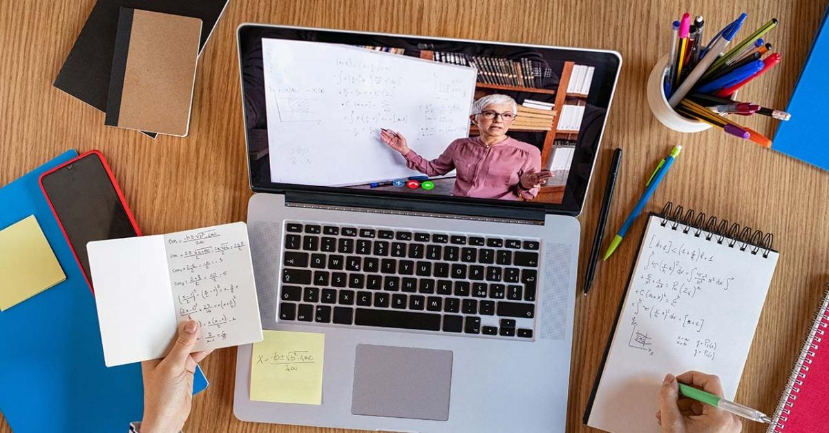 當學生做筆記時,老師通過膝上型計算機的錄影解釋數學題。