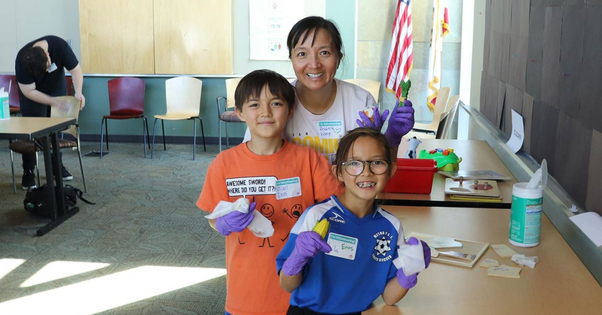 Mother and two children volunteering to clean library materials.