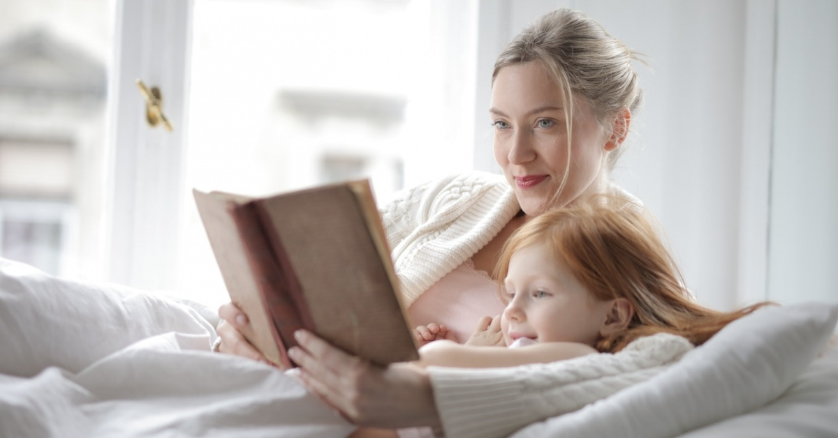 Một người mẹ và cô con gái đọc một cuốn tiểu thuyết trên giường.