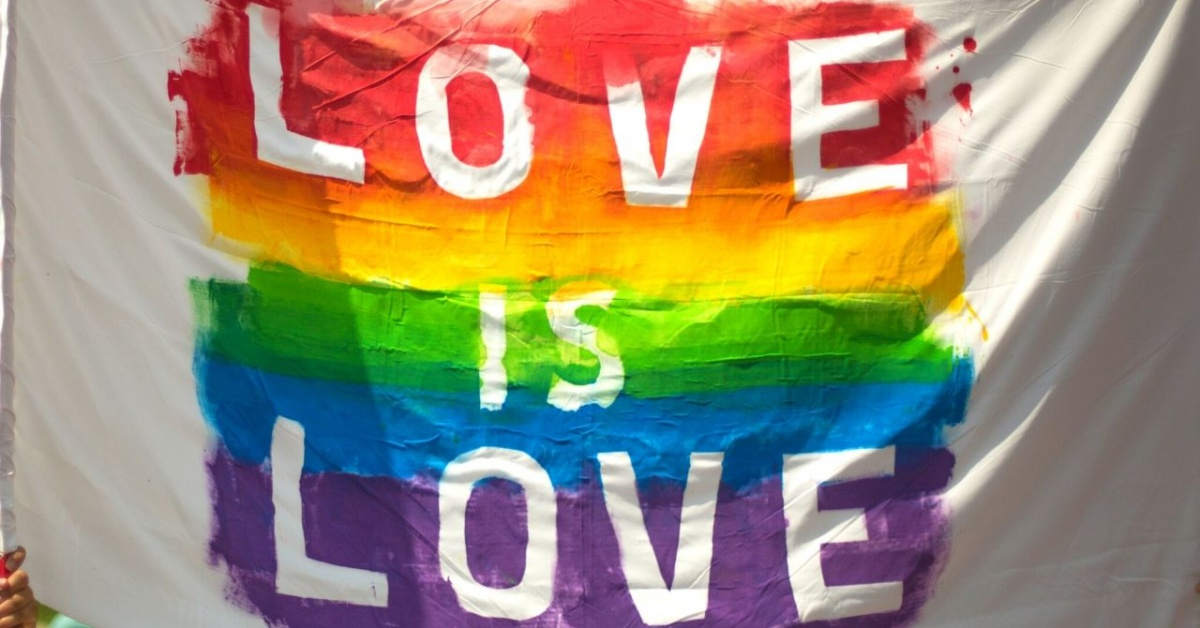 The words love is love in a rainbow on a white sheet.