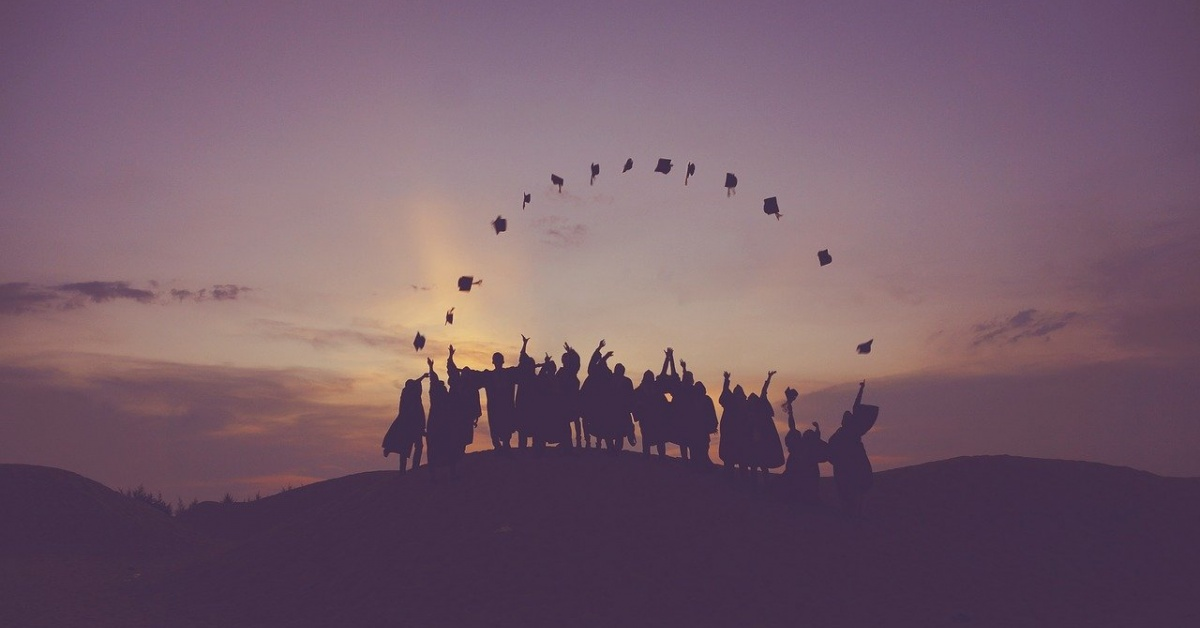 Graduates throw their mortarboards to form an arc before the rising sun.