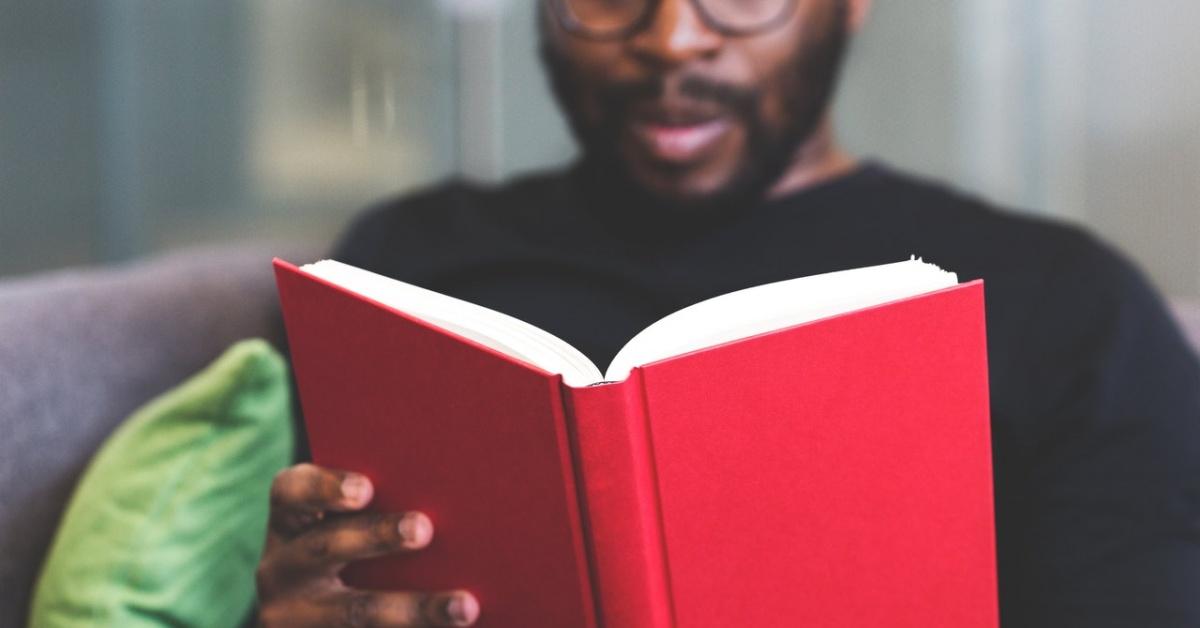 Một người đàn ông đeo kính đọc một cuốn sách.